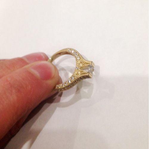 кольцо женское с узорами в лимонном золоте в руке