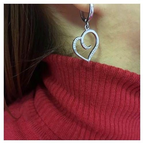 женские серьги в форме сердца в белом золоте на ухе