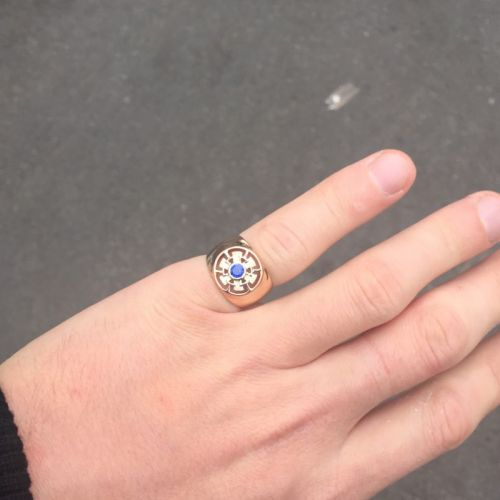 мужская печатка с одним камнем в красном золоте и синим камнем на пальце вдалеке
